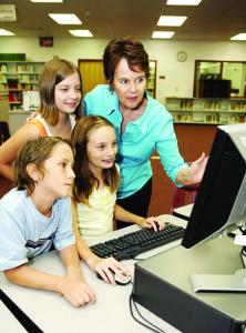 A teacher instructing kids on using the computer.